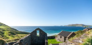 A sunny Irish sky shines on the remains of an old home and the sea