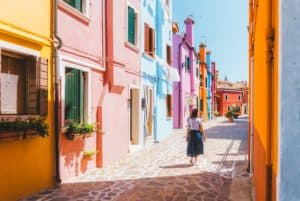 a woman walks the colorful streets in Burano Venice