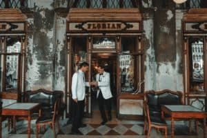 Two men discuss orders at Cafe Florian in Venice