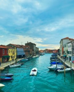 a boat weaves between two islands in Murano Venice