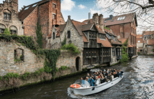 a tour boat glides through the river, constructed much like streets in Bruge belgium
