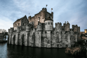 an exterior of the castle of counts looms under a gray sky in belgium