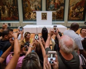 A crowd of people use their phones to take photos of the Mona Lisa