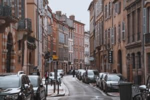 A street view photo of the famous pink and red buildings of Toulouse