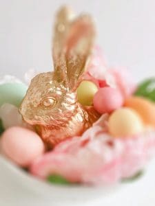 A golden easter bunny in a basket with eggs