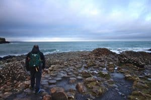 A hiker standing on the shores of the Giants Causeway
