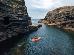 A man kayaking off the coast of County Clare