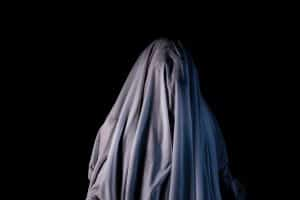 A person pretending to be a ghost with a sheet over their head