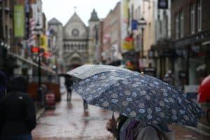A woman carrying an umbrella through rainy Dublin