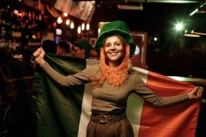 A woman dressed as a leprechaun and holding an Irish flag