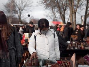 A woman looks through bins at a flea market