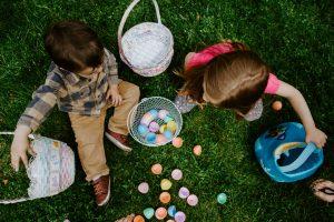 Children putting colourful plastic eggs into baskets