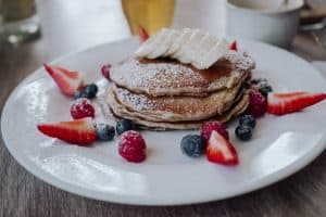 Delicious pancakes topped with powdered sugar and fruit
