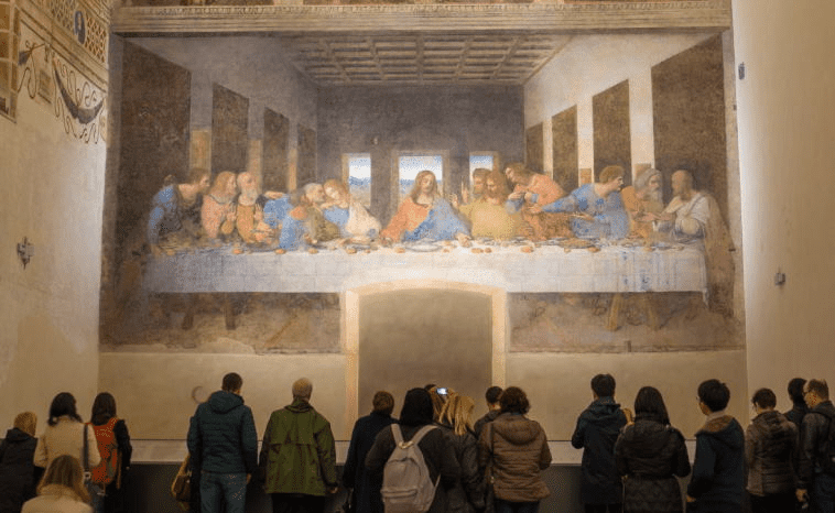 A photo of visitors admiring the mural of the Last Supper