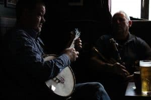 Two musicians sitting in a pub with instruments
