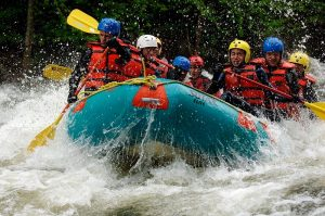 A group of people white water rafting on the hudson river in the Adirondack mountains