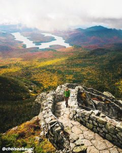 View of Adirondack mountains in the fall with a hiker climbing the trail of a mountain.