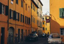 a street in lucca with bright yellow architecture and cobbled stone roads