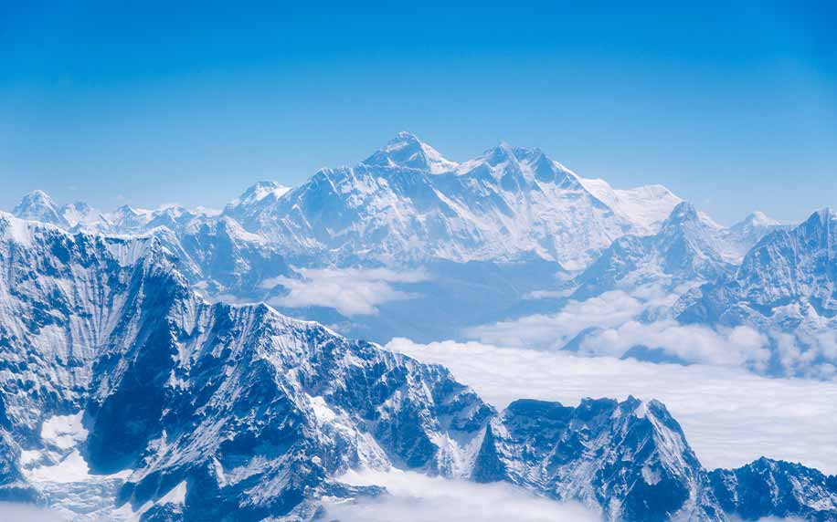 a shot of the mountain range the himalays and mount everest standing above the clouds
