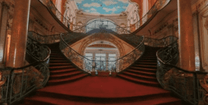 A decadent red staircase leads to mural painted sealing at El Zaafarana Palace in Egypt