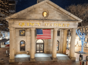 The front entrance of Quincy Market is lit at night in Boston