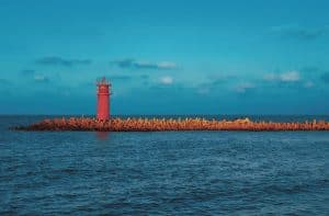Red lighthouse juts out over the water in Pos-el bar