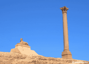 Pillar and sphinx status highlighted in front of a blue sky in Egypt. The Pompay pillar