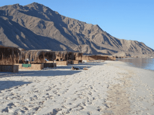 White sand beach with a cascading mountain in the distance in Nuweiba, Sawa beach, Egypt