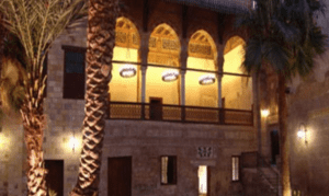The Palace of Prince Taz in Cairo is lit at night and surrounded by palm trees.