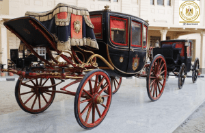 A black and red chariot on display at The Royal Chariots Museum in Egypt.