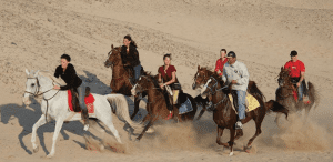 A group of people ride horses through the sand of Sahl Hashish
