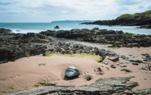 The soft sand meets the rocky entrance to the water in ballyquin beach in Ireland