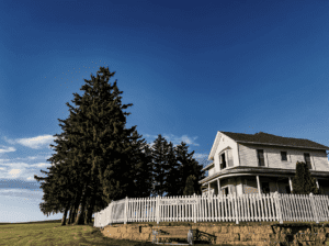 A colonial looking house with a white picket fence in America