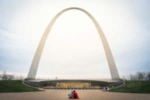 The Gateway Arch stands tall in front of a couple in America