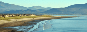 The mountains of Kerry are seen the distance of Inch Beach in Ireland