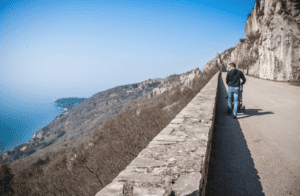 A man pushing a strolled walks along the Napoleonic Road in Trieste