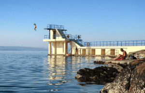A man jumps off the platform in Salthill located in Galway, Ireland