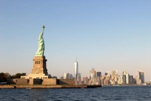 A wide shot of the back of the Statue of Liberty overlooking New York City