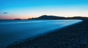 The rocky beach of trawmore bay can barely be seen in the diminishing sunset of Ireland