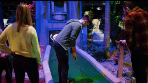 A man lines up for a putt at an indoor golf course in Belfast