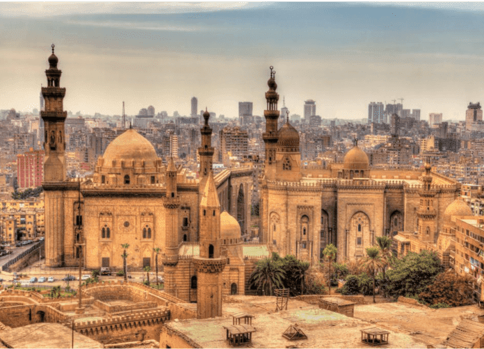 A mosque set in the center with the modern city of Cairo in the distance.
